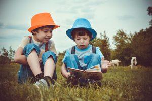 Zwei Kinder sitzen auf der Wiese und lesen ein Buch.